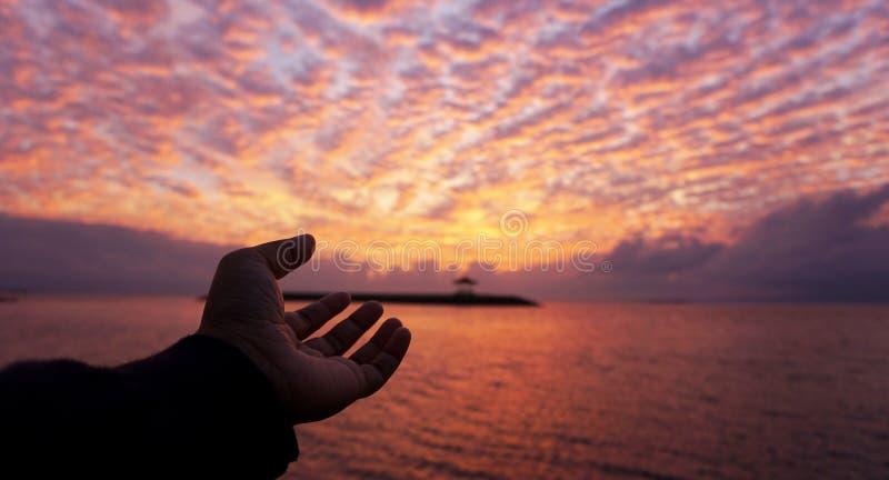 Ręka dosięga za świetle Łamliwości i nadziei pojęcie z pięknym wschód słońca tłem obraz stock