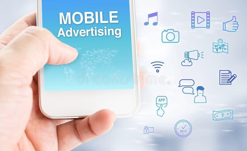 Ręka dotyka telefon komórkowy z mobilnym reklamy słowem z featur fotografia stock