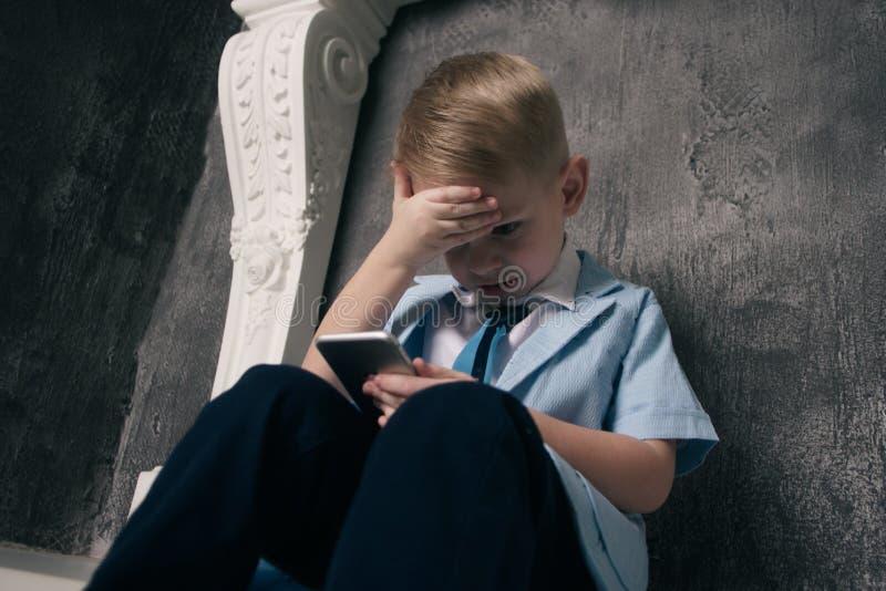 Ręka dzieciak używa mądrze telefon Portret uśmiechnięty chłopiec mienia telefon komórkowy obrazy royalty free