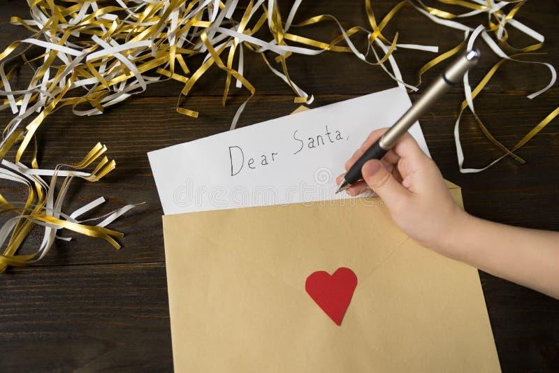 Ręka dziecka pisze list do Mikołaja, koperta Tinsel, drewniane tło obrazy stock