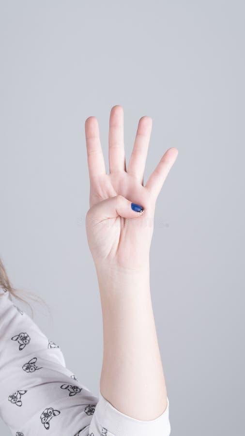 Ręka dziewczyna pokazuje cztery palca fotografia royalty free