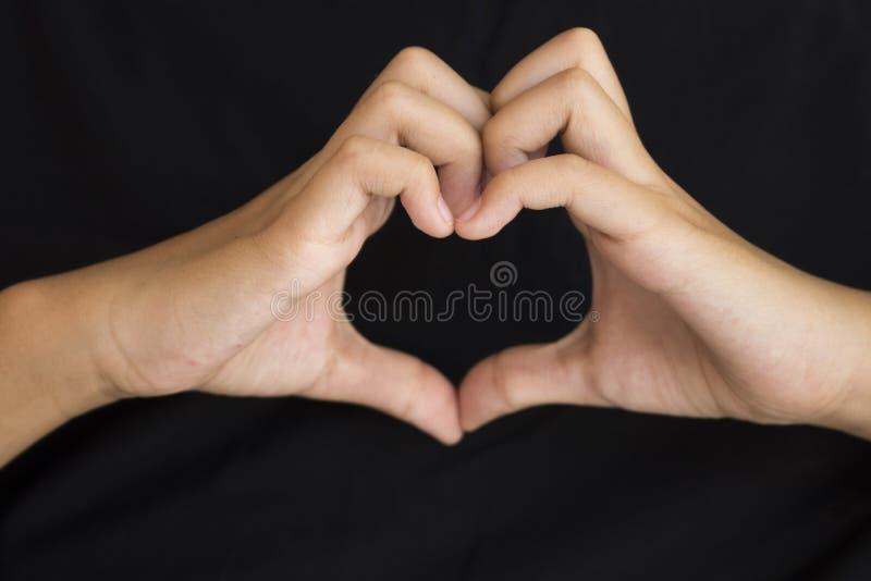 Ręka dziewczyna symbolu gesta serce wysyła miłości na czerni zdjęcie royalty free