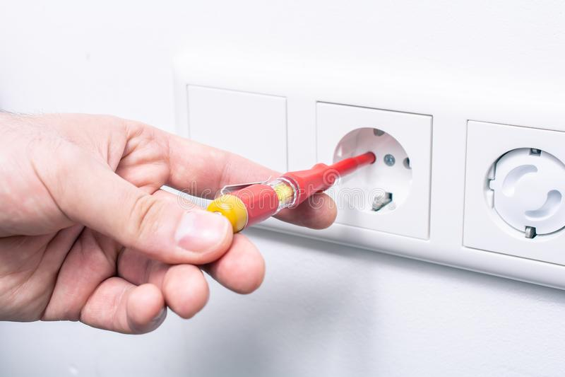 Ręka elektryk Trzyma faza testra W Ściennej nasadce Rozjarzony światło Wskazuje Aktywnego prąd obrazy stock