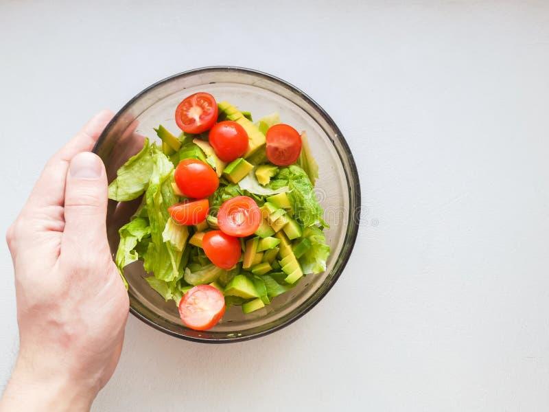 Ręka gniesie wapno nad jarską sałatką zrobi od avocado, pomidorów, ogórka i basila, obraz royalty free