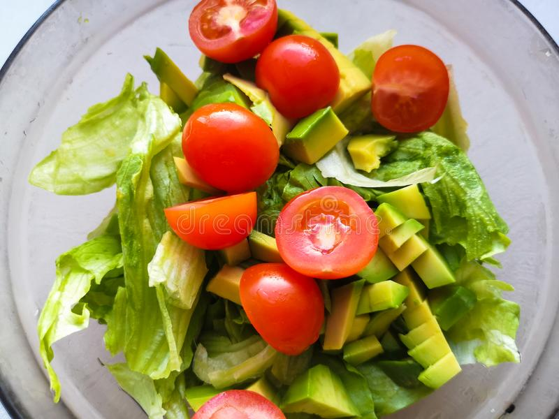 Ręka gniesie wapno nad jarską sałatką zrobi od avocado, pomidorów, ogórka i basila, zdjęcia stock
