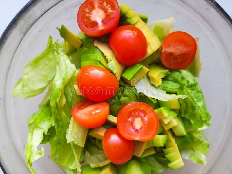 Ręka gniesie wapno nad jarską sałatką zrobi od avocado, pomidorów, ogórka i basila, zdjęcie royalty free