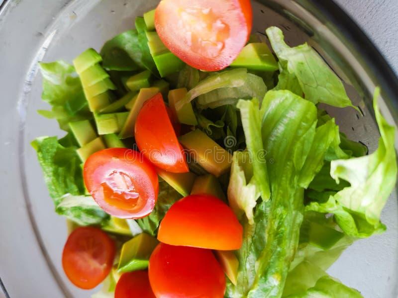 Ręka gniesie wapno nad jarską sałatką zrobi od avocado, pomidorów, ogórka i basila, obrazy stock
