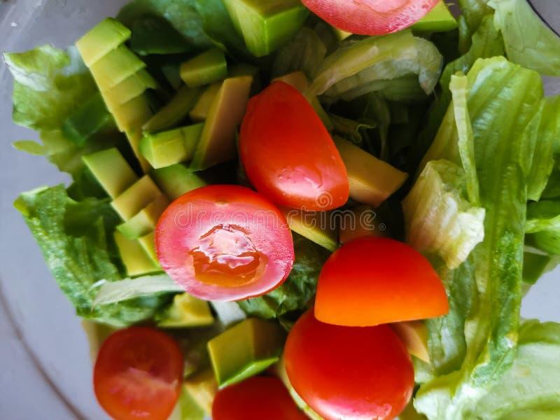 Ręka gniesie wapno nad jarską sałatką zrobi od avocado, pomidorów, ogórka i basila, zdjęcia royalty free