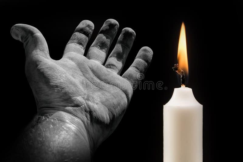 Ręka i świeczka na czarnym tle na temat śmierci obraz stock