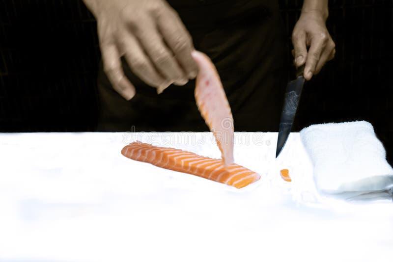 Ręka Japoński szefa kuchni przecinania grubas daleko od łososia zdjęcia stock