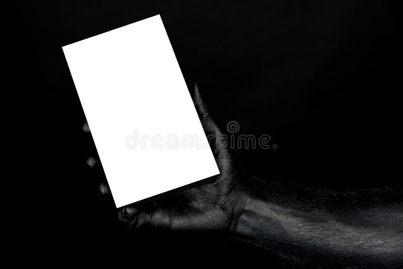 Ręka jest całkowicie w czarnej farbie trzyma białego prześcieradło z przestrzenią dla inskrypcji zdjęcie stock