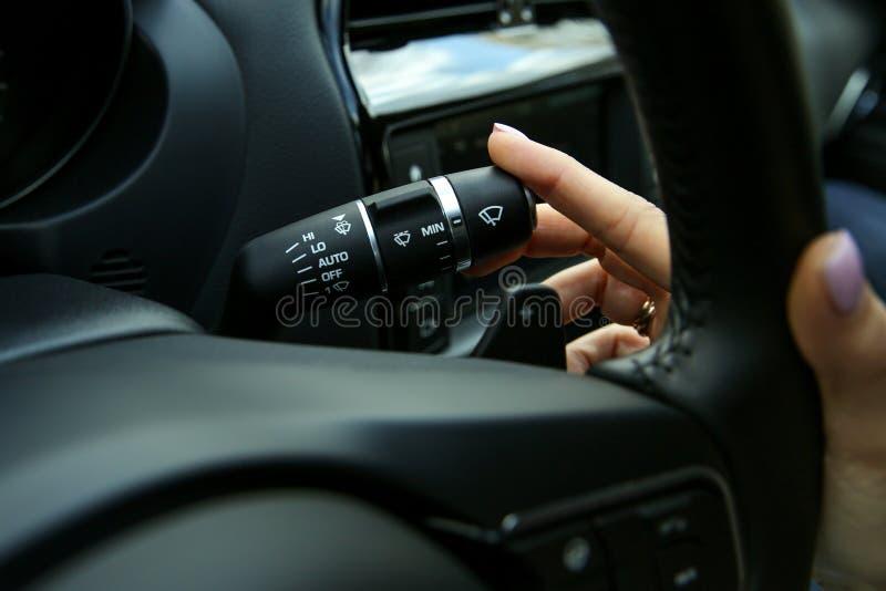 Ręka kierowca obraca dalej wipers na samochodzie zamkniętym w górę obraz royalty free