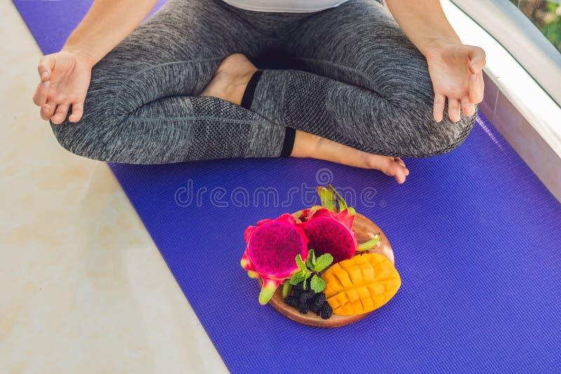 Ręka kobieta medytuje w joga pozie, siedzi w lotosie z owoc przed owoc, mango i morwą jej smoka, obrazy royalty free