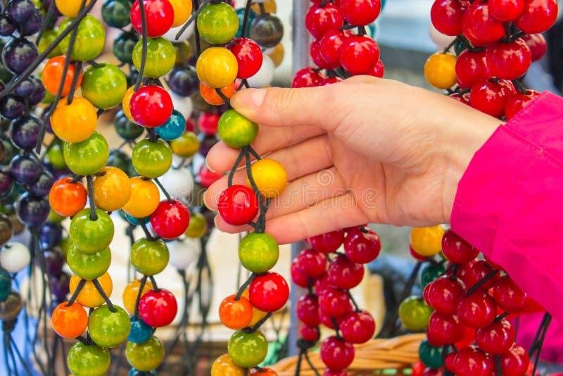 Download Ręka Kobieta Z Drewnianą Kolią Na Kramu Przy Bazarem Obraz Stock - Obraz złożonej z rzemiosło, sprzedaż: 57653523