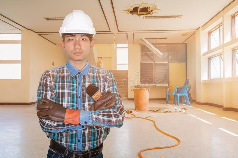 Ręka krzyż inżyniera mienia farby muśnięcie w zatrudnienie naprawy wody przecieku kropli wn?trza budynku biurowym zdjęcia stock