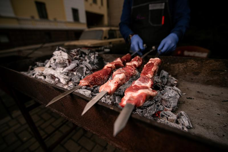 Ręka kucharzi w błękitnych rękawiczkach trzymają skewers z mięsem na grillu zdjęcie royalty free