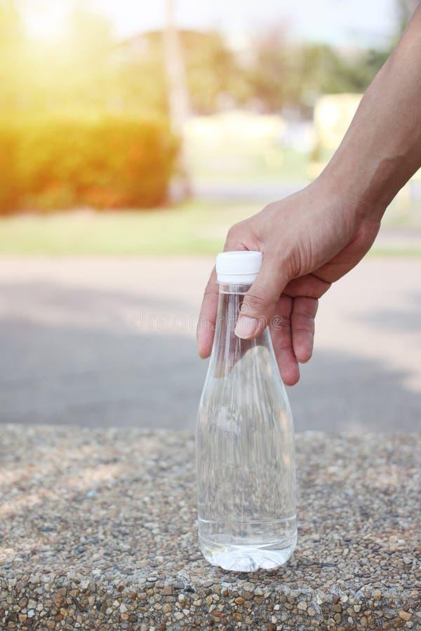 Ręka mężczyzna trzyma butelkę woda pitna obrazy royalty free