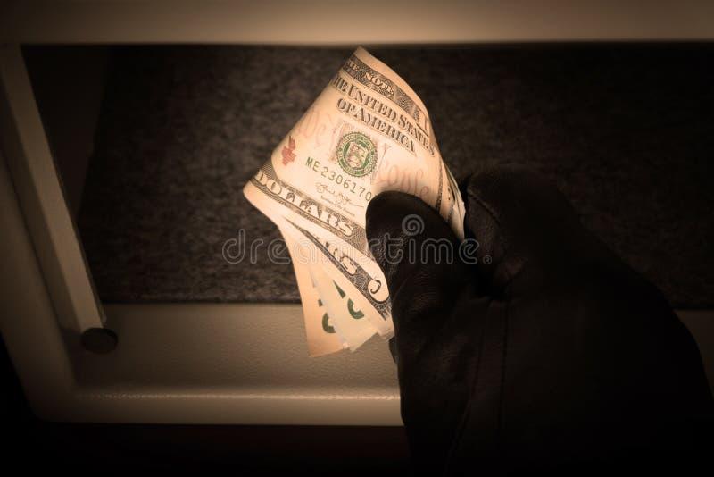 R?ka m??czyzna w czarnej r?kawiczce trzyma dolar?w ameryka?skich rachunki Otwiera metal skrytk? Poj?cie oszcz?dzanie pieni?dze w  zdjęcie stock