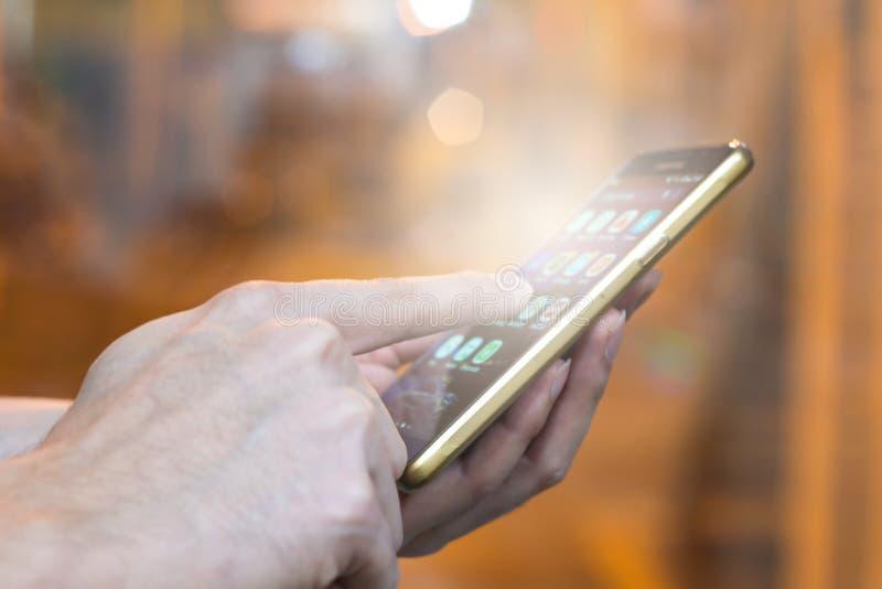 Ręka mężczyzna wskazuje palec na parawanowym smartphone na kontrolnego pokoju półdupkach zdjęcie stock