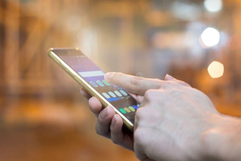 Ręka mężczyzna wskazuje palec na parawanowym smartphone na kontrolnego pokoju półdupkach fotografia stock