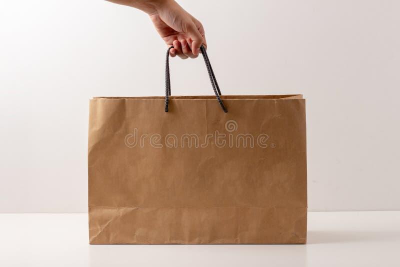 Ręka młody caucasian trzyma papierowego torba na zakupy zdjęcia royalty free