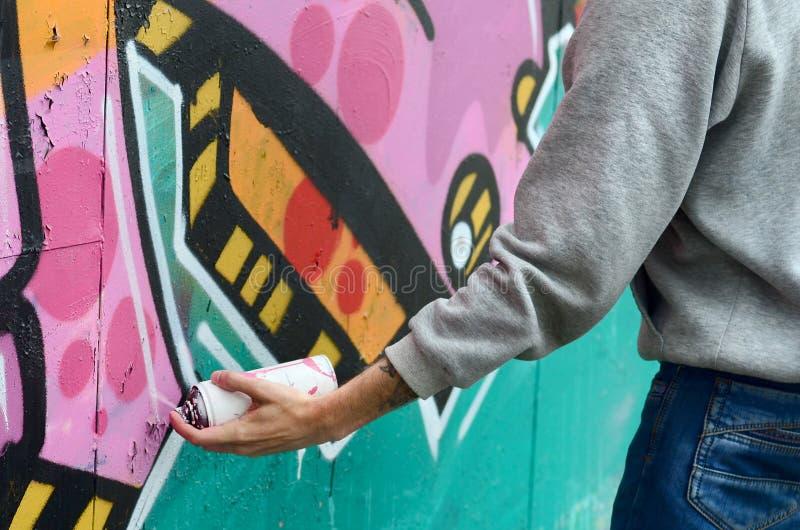 Ręka młody facet w szarym hoodie maluje graffiti w menchiach i fotografia stock