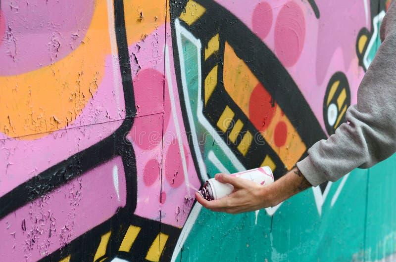 Ręka młody facet w szarym hoodie maluje graffiti w menchiach i zdjęcia royalty free
