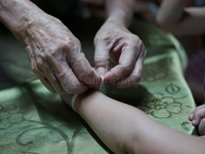 Ręka macha białego smyczkowego Sai grzech wokoło jej wnuczek ręk stara kobieta - Tajlandzki tradycyjny błogosławieństwo od fotografia royalty free