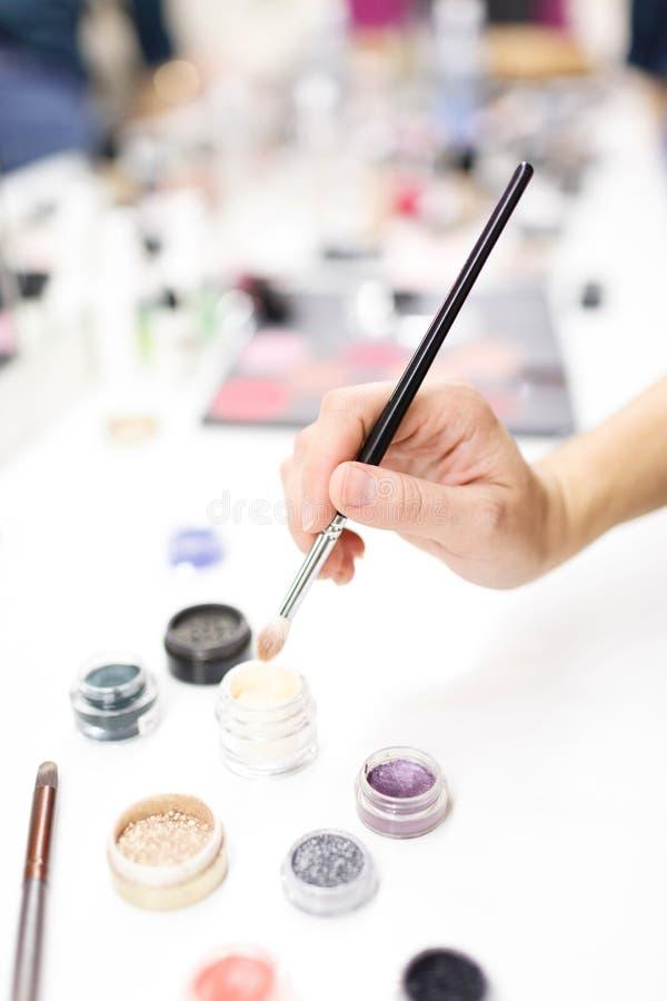 Ręka makijażu artysta utrzymuje muśnięcie Barwioni okręgi confetti dla projekta zdjęcia royalty free