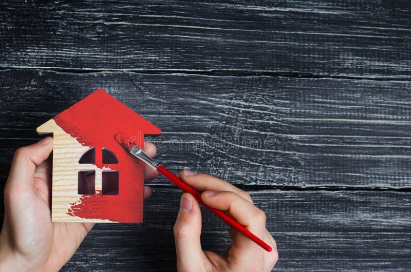 Ręka maluje dom wewnątrz czerwony kolor Pojęcie naprawa, hobby, praca Naprawa i obraz drewniane domowe figurki dziecko tła ręce d fotografia royalty free