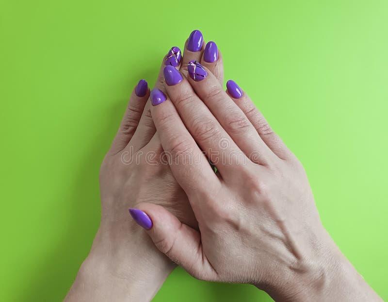 Ręka manicure'u połysku fiołkowy projekt na barwionym papierowym modnym splendorze minimalnym zdjęcie royalty free