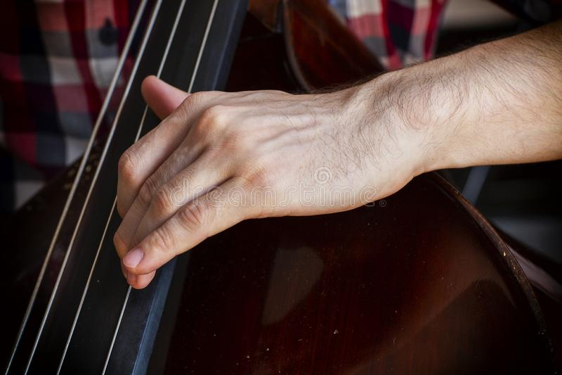 Ręka muzyk bawić się na kontrabasowym zbliżeniu zdjęcie royalty free