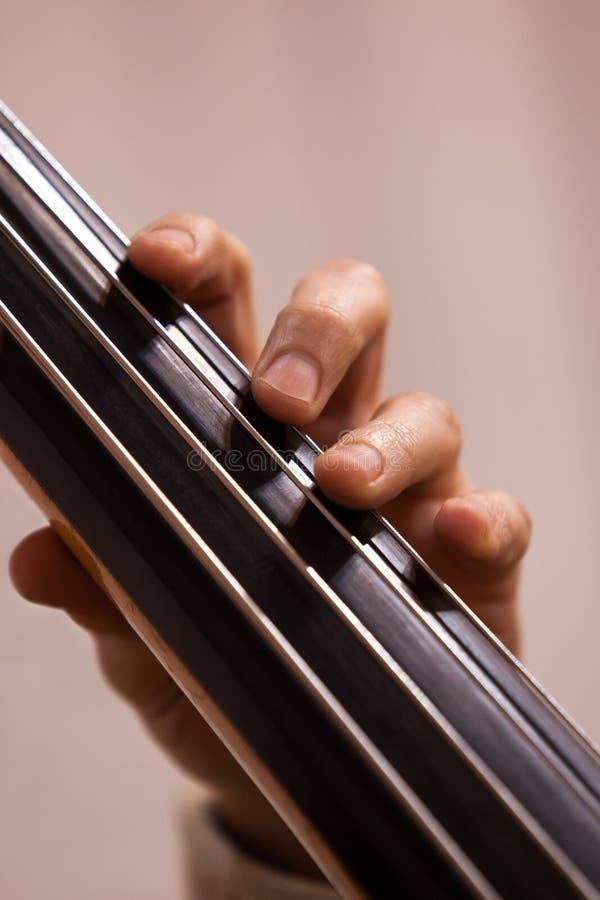 Ręka muzyk na basowych sznurkach obraz royalty free