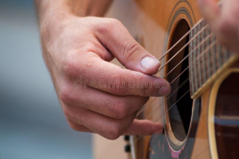 Ręka muzyk na ludowej gitarze w ulicie obrazy stock