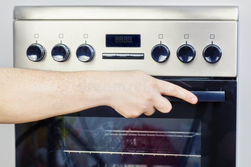 Ręka na elektrycznej kuchence zdjęcie royalty free
