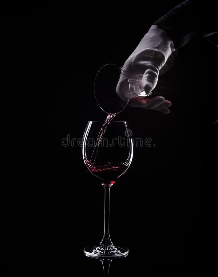 Ręka nalewa czerwone wino od dekantatoru szkło obraz stock