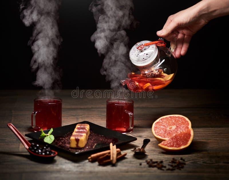 R?ka nalewa gor?cej herbaty od szklanego czajnika Paruj?ca herbata w szk?ach Wy?mienicie Japo?ski s?odki deser na ciemnym tle fotografia royalty free