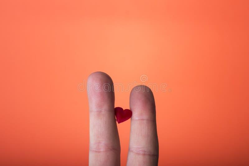 ręka odizolowywająca na pomarańczowej czerwieni tle zdjęcia stock