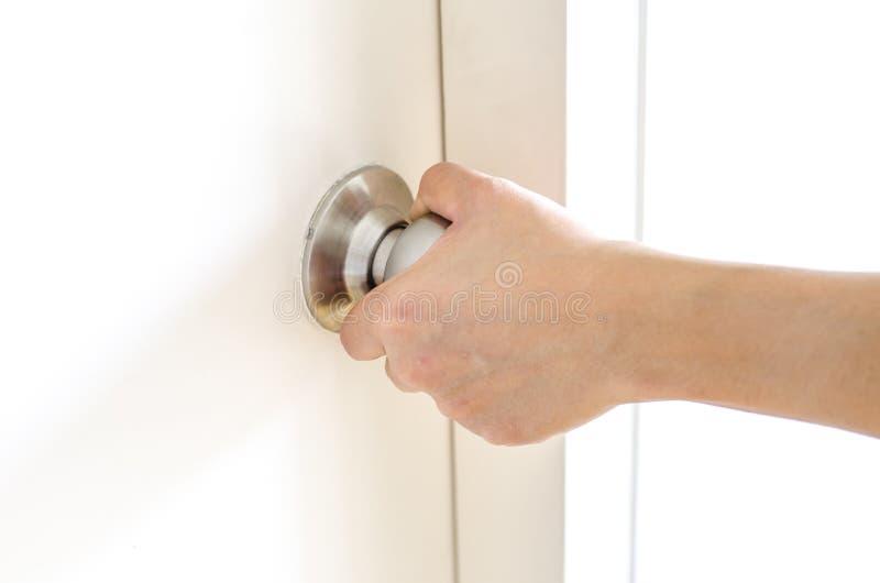 Ręka otwiera drzwiową gałeczkę, biały drzwi zdjęcie royalty free