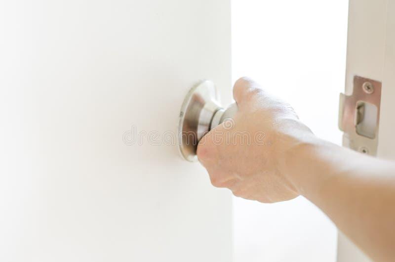 Ręka otwiera drzwiową gałeczkę, biały drzwi obrazy royalty free