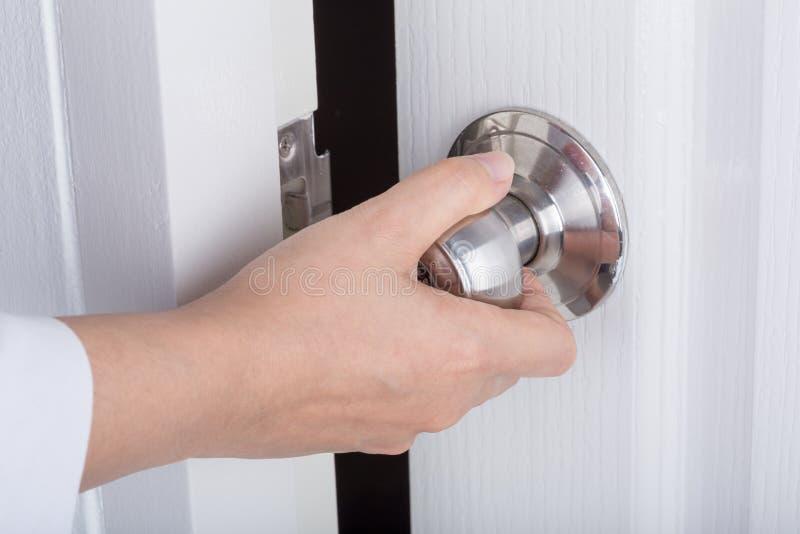 Ręka otwiera drzwiową gałeczkę na białym drzwi obraz stock
