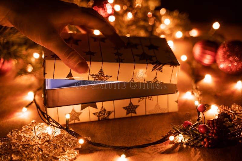 Ręka otwiera prezenta pudełko, trzyma prezent, drewnianego tło z mruganie girlandą i choinki, zdjęcie stock
