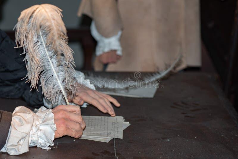 Ręka pisze liście z pióropuszem fotografia stock