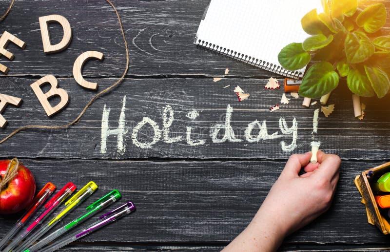 Ręka pisze wakacjach na czarnej desce drewniane deski Pojęcie szkoła podstawowa Kreatywnie chaos Studencki ` s biurko t obraz stock