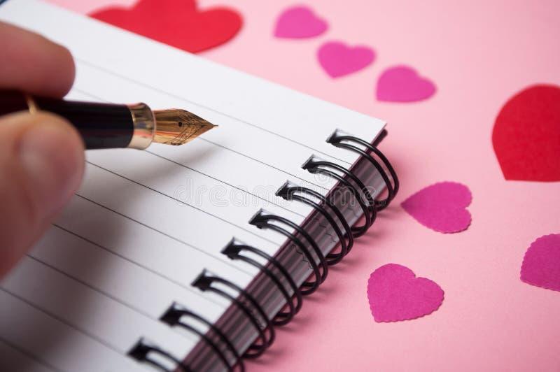 ręka pisze z rocznika piórem na spirales nutowej książce z papierowymi sercami na różowym tle mężczyzna obrazy stock