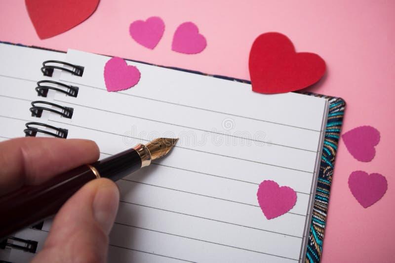 ręka pisze z rocznika piórem na spirales nutowej książce z papierowymi sercami na różowym tle mężczyzna zdjęcia royalty free