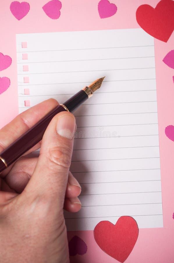 Ręka pisze z rocznika piórem na spirales nutowej książki stronie z papierowymi sercami na różowym tle mężczyzna zdjęcie stock