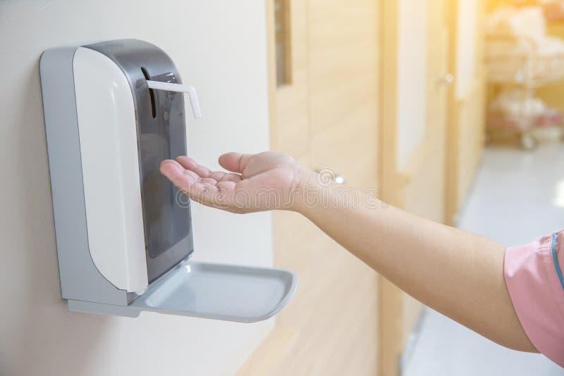 Ręka pod automatyczną alkohol aptekarką obrazy stock