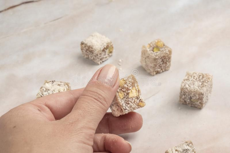 Ręka - podnosi tureckiego zachwyt z koksem i pistacją obraz stock