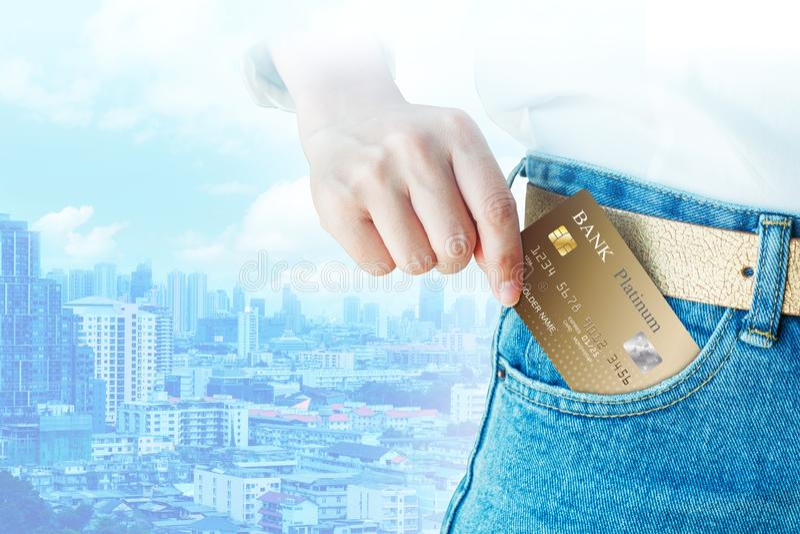 Ręka - podnosi up realistycznego kredyt lub kartę debetową na biznesowym mieście obraz royalty free